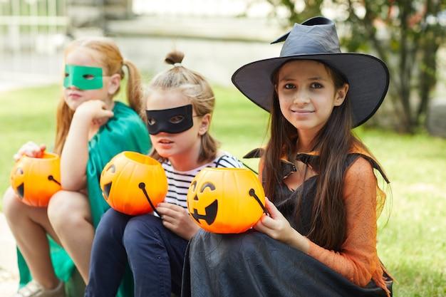 Retrato de amigos felizes em fantasias com abóboras sorrindo para a câmera ao ar livre na festa de halloween
