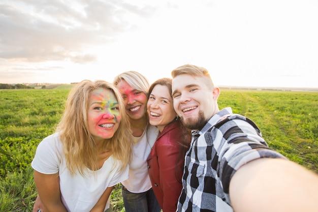 Retrato de amigos felizes no festival de cores holi tirando uma selfie