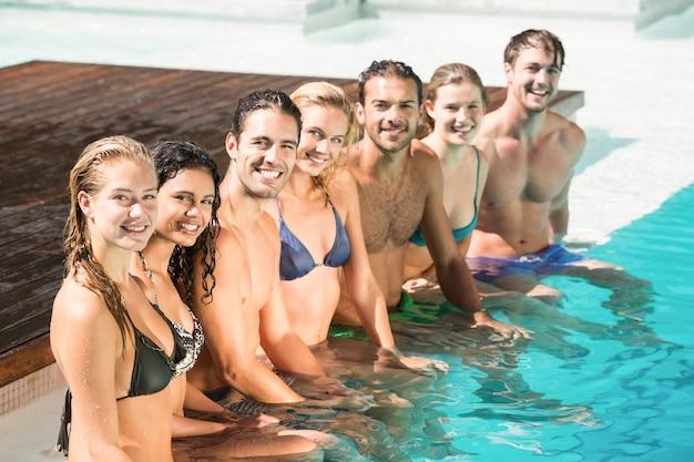 Retrato de amigos sentado na piscina