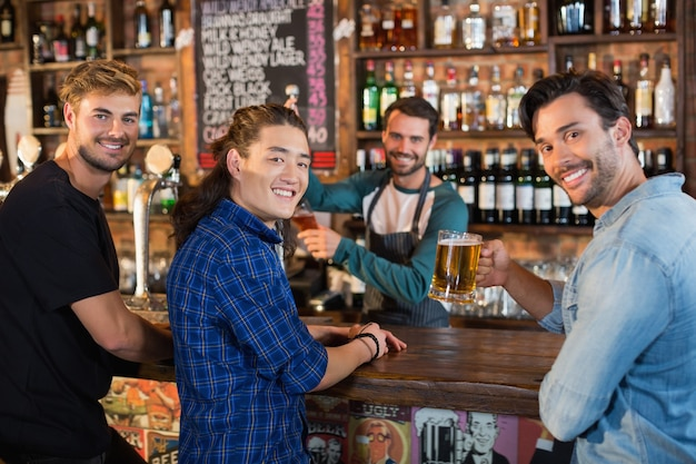 Retrato de amigos sorridentes com bartender