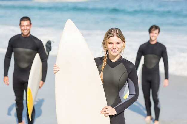 Retrato de amigos surfistas com pé de prancha de surf na praia