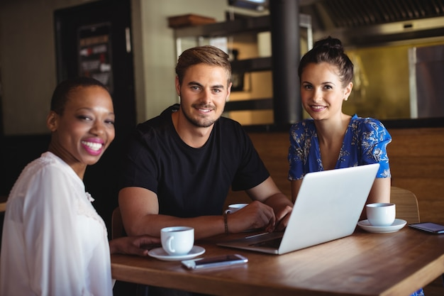 Retrato de amigos usando laptop enquanto tomam café