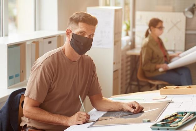 Retrato de arquiteto barbudo maduro usando máscara enquanto está sentado na mesa de desenho ao sol,