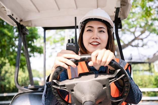 Retrato de arquiteto de mulher com carrinho de golfe e comunicação via walkie-talkie. vista traseira do contratante no fundo de edifícios de casas modernas no jardim.