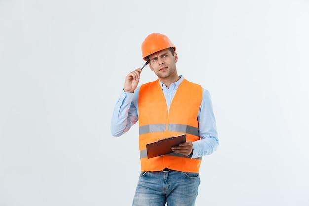 Retrato de arquiteto ou engenheiro sério escrevendo ou fazendo anotações em uma prancheta isolada no fundo branco