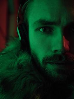 Retrato de arte néon moda masculina. modelo de cara bonito posando ao ar livre e ouvindo música em fones de ouvido em filtros de vermelhos e verdes. meia cara
