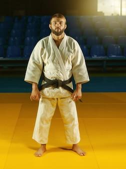 Retrato de artista marcial em quimono branco e faixa preta em salão de esportes
