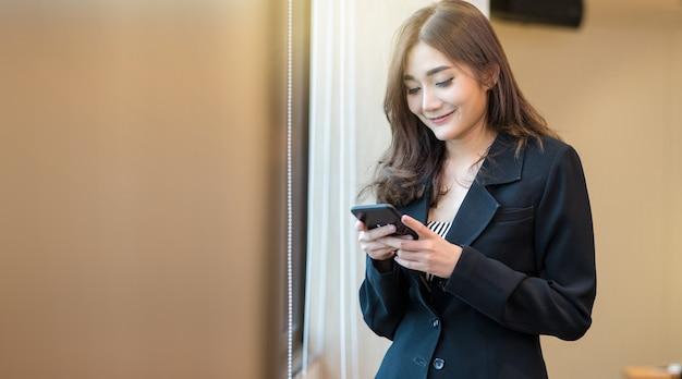 Retrato, de, asiático, executiva, em, formal, paleto, usando, a, esperto, telefone móvel, com, sorrizo, ato