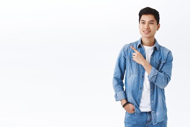 Retrato de asiático jovem bonito e saudável olhando e apontando o canto superior esquerdo, com emoção satisfeita, escolha excelente, posição de trabalho perfeita, parede branca de pé