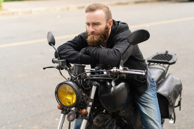 Retrato, de, assento homem, ligado, motocicleta, com, pensativo, expressão
