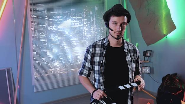Retrato de assistente de produtor, sorrindo para a câmera e dando ação com claquete de cinema.