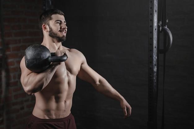 Retrato de atleta crossfit sorridente, exercitando-se com um kettlebell no ginásio.