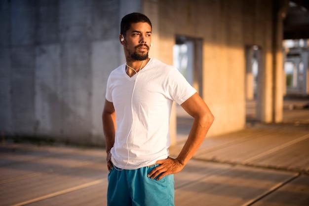 Retrato de atleta desportivo em forma com fones de ouvido se concentrando para o treinamento
