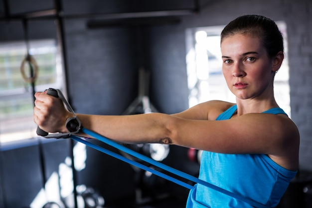 Retrato de atleta feminina, esticando a banda de resistência