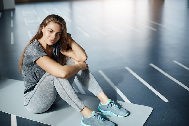 Retrato de atleta feminina no ginásio vazio, descansando sentado na esteira de ioga entre os exercícios. mulher no conceito de esporte.