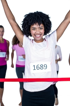 Retrato de atleta feminino ganhador feliz cruzando linha de chegada com braços levantados