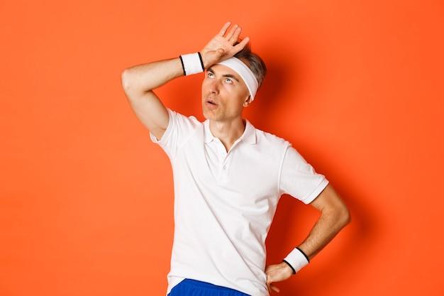 Retrato de atleta masculino irritado, revirando os olhos e palma da mão, parecendo incomodado