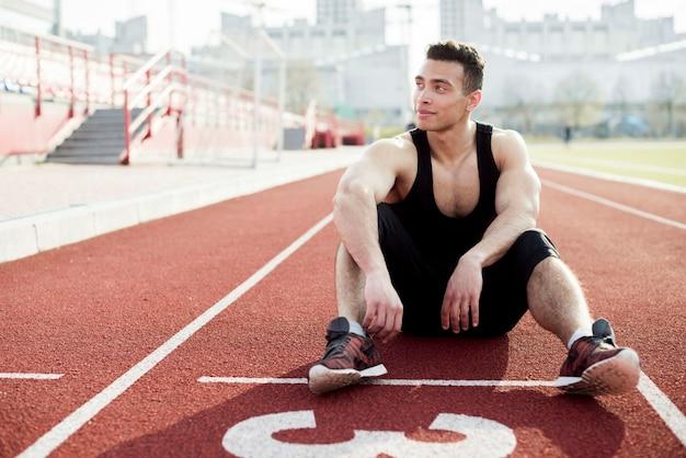 Retrato de atleta masculino relaxante na pista de corrida vermelha