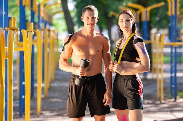 Retrato de atletas profissionais caucasianos e homem bonito e mulher morena com fitas cinesiológicas nos corpos