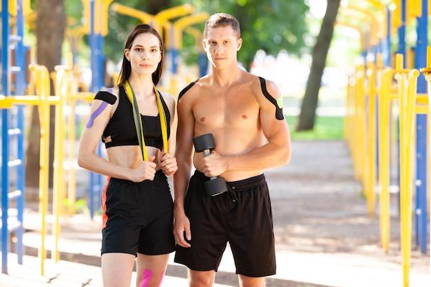 Retrato de atletas profissionais, homem bonito e mulher morena com fitas cinesiológicas nos corpos