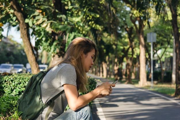 Retrato, de, atraente, feliz, mulher asian, segurando, smartphone, enquanto, sentando, ligado, à margem estrada, em, a, cidade