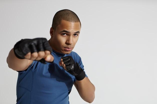 Retrato de atraente jovem mestiço do sexo masculino com cabeça raspada, exercitando-se no ginásio, em pé na parede branca, com o punho erguido na direção da câmera, dando um soco. conceito de boxe, kickboxing e artes marciais