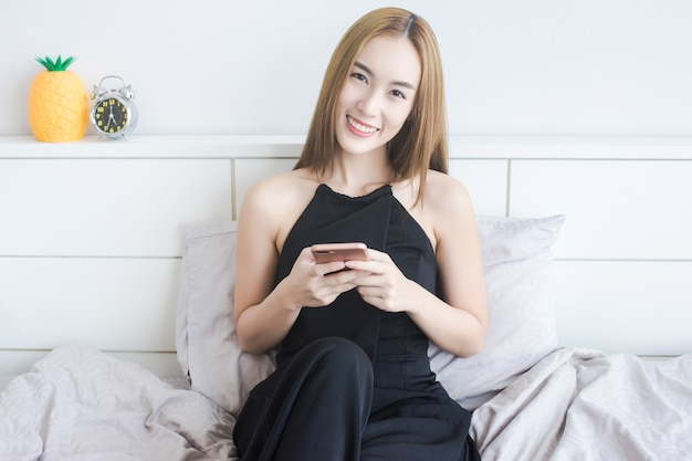 Retrato, de, atraente, mulher asian, sentar-se cama, enquanto, uso, smartphone