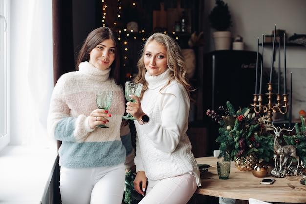 Retrato de atraentes amigas brancas comemorando modestamente o ano novo juntas