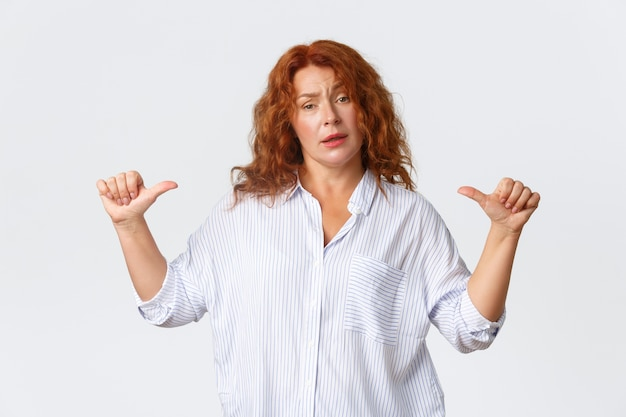 Retrato de atrevida empreendedora profissional, mulher ruiva de meia-idade, apontando para si mesma para garantir que ela possa resolver qualquer problema. parecendo confiante, exibicionista sobre a parede branca.
