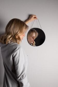 Retrato de auto-reflexão da mulher no espelho contra a parede cinza