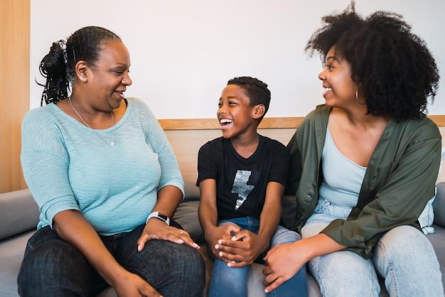 Retrato de avó afro-americana, mãe e filho passando um bom tempo juntos em casa. conceito de família e estilo de vida.