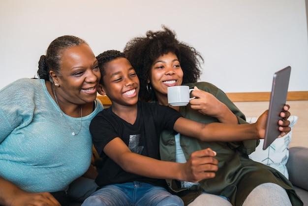 Retrato de avó afro-americana, mãe e filho tirando uma selfie com tablet digital em casa. conceito de tecnologia e estilo de vida.