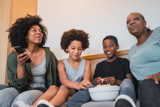 Retrato de avó afro-americana, mãe e filhos assistindo a um filme e comendo pipoca enquanto está sentado no sofá em casa. conceito de família e estilo de vida.