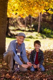 Retrato de avô e neto brincando com folhas de outono