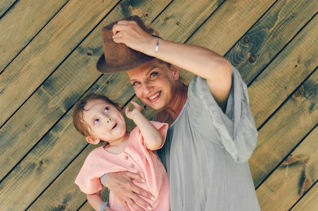 Retrato de avó e sua neta em clothers de estilo rural em fundo de madeira