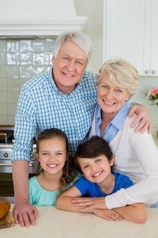 Retrato de avós e netos em pé na cozinha