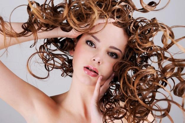 Retrato de baixo ângulo da bela mulher com longos cabelos cacheados