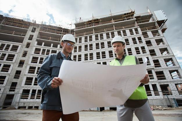 Retrato de baixo ângulo de dois engenheiros discutindo plantas baixas no espaço de cópia do canteiro de obras