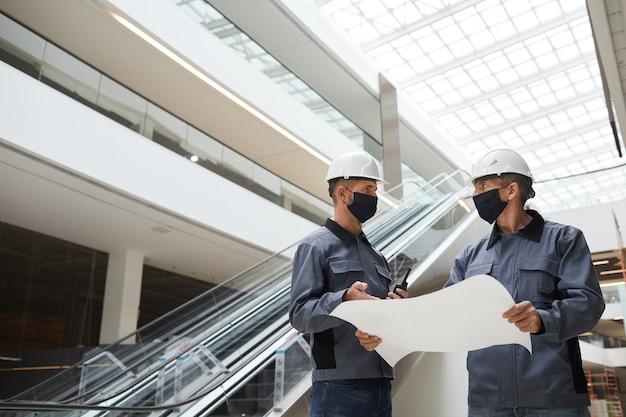 Retrato de baixo ângulo de dois trabalhadores da construção civil usando máscaras e discutindo planos em um shopping center ou prédio comercial.