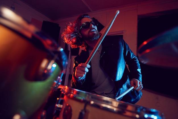 Retrato de baixo ângulo de um jovem bonito tocando bateria durante show de música em luzes brilhantes