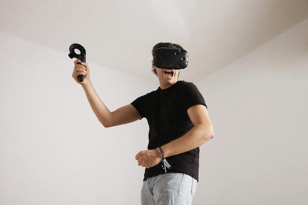 Retrato de baixo ângulo de um jovem jogador de aparência assustadora em jeans, camiseta preta em branco e fone de ouvido vr