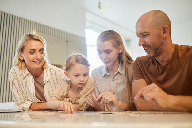 Retrato de baixo ângulo de uma família moderna com duas crianças resolvendo quebra-cabeças juntas enquanto aproveitam o tempo dentro de casa