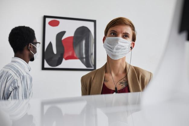 Retrato de baixo ângulo de uma jovem usando máscara na galeria de arte, enquanto olha esculturas e explora a exposição.