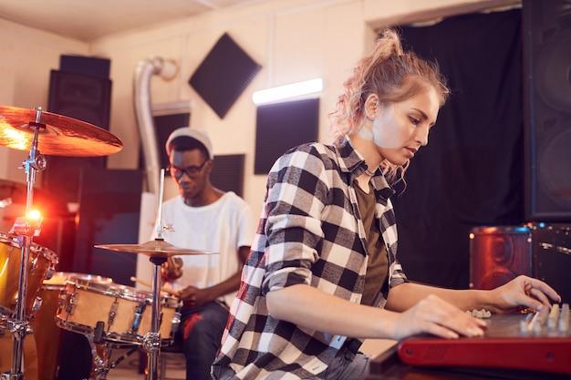 Retrato de banda contemporânea escrevendo música em estúdio de gravação com foco em jovem