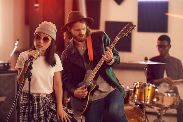 Retrato de banda contemporânea tocando música durante ensaio ou show em estúdio mal iluminado