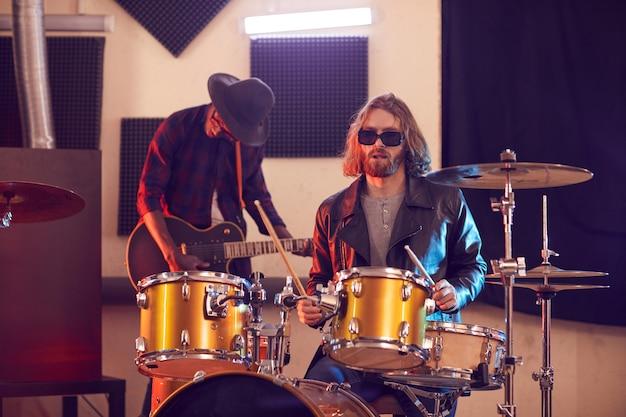 Retrato de banda de rock contemporâneo com foco em homem de cabelos compridos tocando bateria em primeiro plano