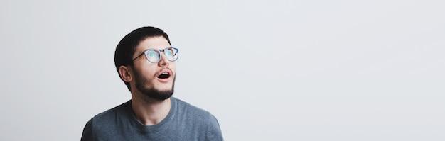 Retrato de banner panorâmico de jovem chocado com óculos redondos