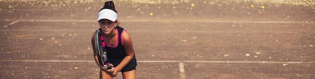 Retrato de banner panorâmico de menina adolescente jogando tênis na quadra.
