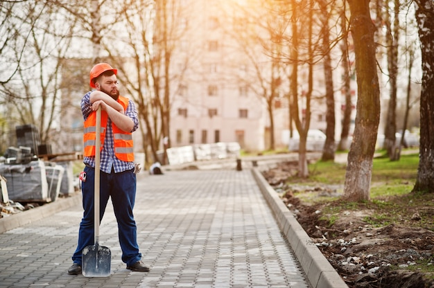 Retrato de barba brutal trabalhador homem terno trabalhador da construção civil no capacete de segurança laranja contra pavimento com pá na mão.