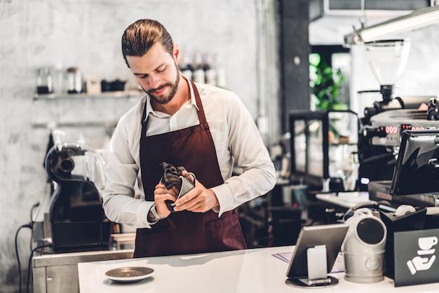 Retrato de barista barbudo bonito pequeno empresário proprietário sorrindo e segurando a xícara de café no café ou cafeteria. barista masculino em pé no café